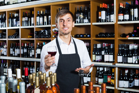 promoting: portrait of male seller in uniform promoting to taste wine before purchasing it in wine store