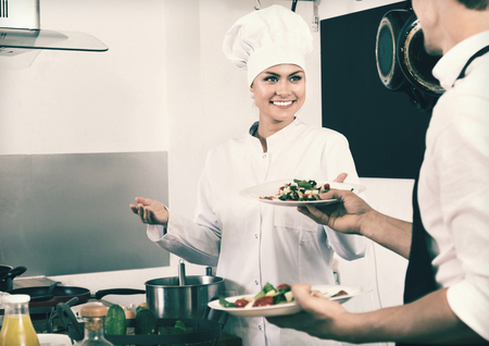 diligent: Portrait of diligent  smiling woman cook giving to waitress ready to serve salad