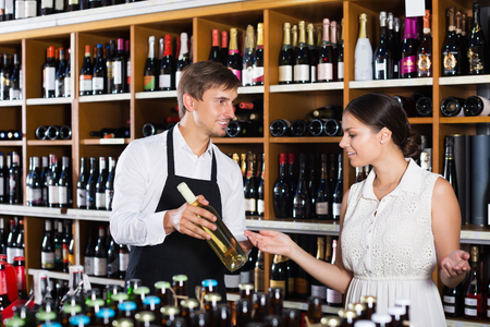 wine store: Smiling seller man wearing apron helping to buy bottle of wine to woman customer in wine store