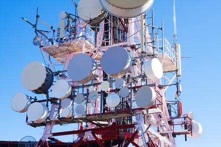 Nahaufnahme von Telekommunikationsmastantennen mit blauem Himmel am sonnigen Tag Standard-Bild - 64917355