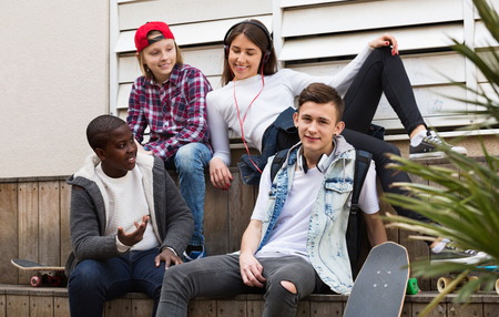 blabbing: Group of ordinary  teenage friends relaxing and chatting in town square
