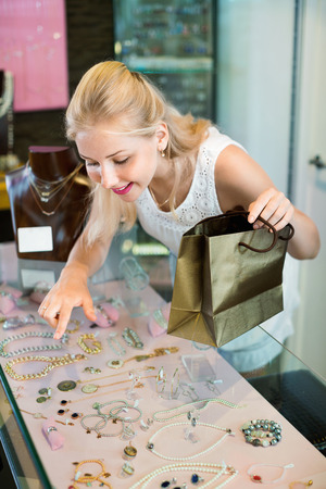 personal shopper: Portrait of young cheerful charming woman standing next to glass showcases in shop with bijouterie
