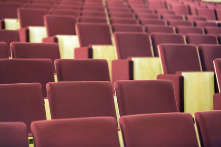 lecture theatre: Comfortable seats with red upholstery in audience hall