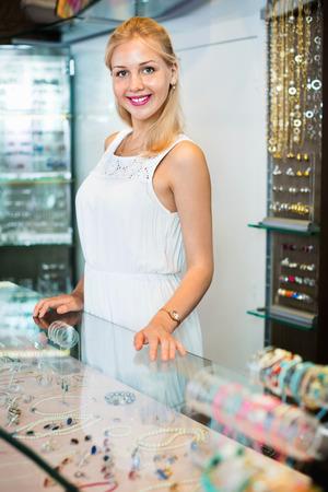 diligente: Retrato de alegre hembra joyero diligente con el vidrio presenta en la tienda con bisutería Foto de archivo