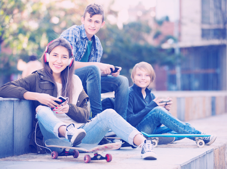 16s: Three european teenagers with smartphones in autumn day outdoors