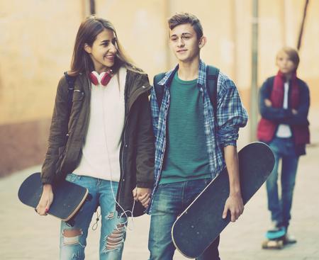 celos: adolescente celosa y su sonrisa amigos españoles después de un conflicto al aire libre