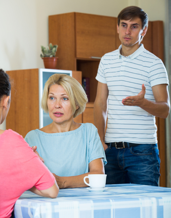 squabble: Young spouses and mother-in-low arguing indoors