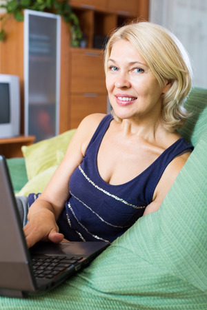 Happy mature woman using a laptop in her home closeup