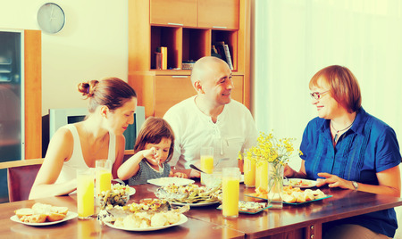 multigeneration: multigeneration family  eating fish with vegetables at home together