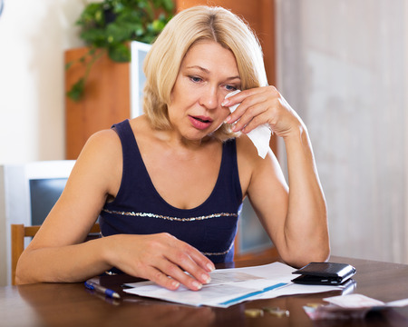 Portrait of blond woman reading letter on paper at the table in home