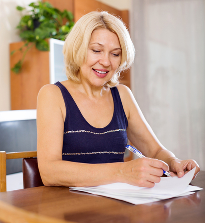 home office interior: Happy smiling woman filling in paper at home or office interior