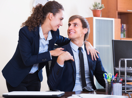 tempter: Sexual harassment in office: smiling boss flirting with employee at workplace Stock Photo