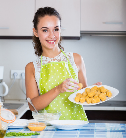 crocchette: Happy housewife cooking breadcrumbed croquettes in domestic kitchen