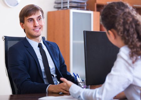 conduction: Young professional teaching new clerk in practice at company