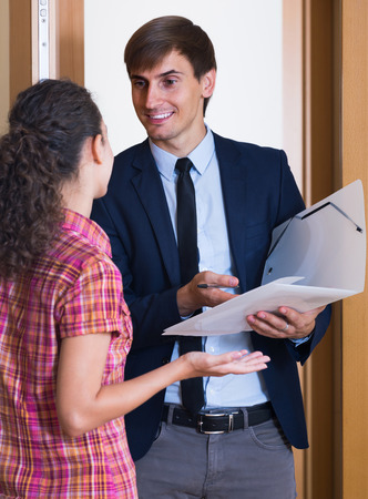 householder: happy european commercial agent greeting householder and selling subscriptions in hall