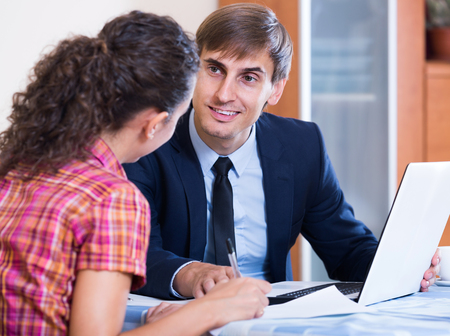 agency agreement: adult spanish insurance agent and customer discussing agreement terms and smiling Stock Photo
