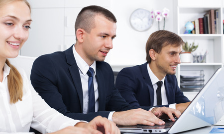 formalwear: serious business male assistant wearing formalwear sitting with coworkers in company office Stock Photo
