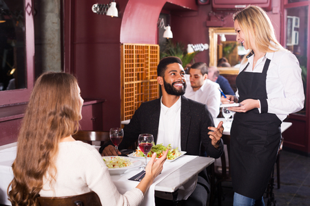 clase media: Happy young spouses having date in middle class restaurant. Focus on blonde girl Foto de archivo