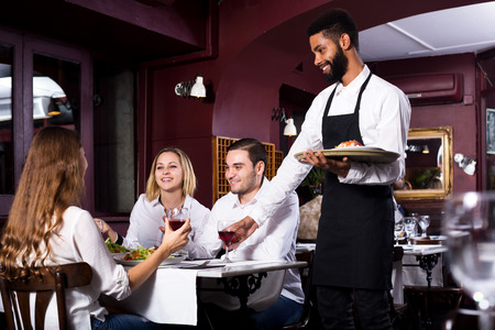clase media: Retrato de los adultos en el restaurante de clase media y atractivo camarero negro