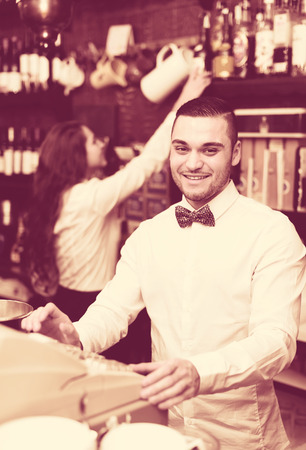 checkout counter: Smiling friendly male bartender working in a bar with a checkout counter