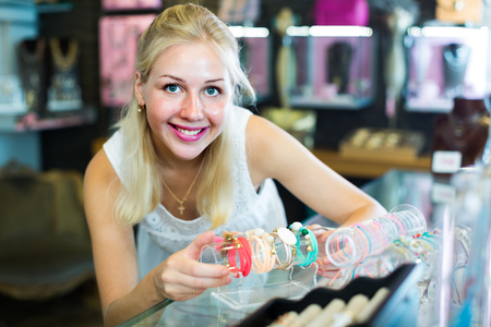 personal shopper: positive woman seller showing various bracelets in bijouterie boutique