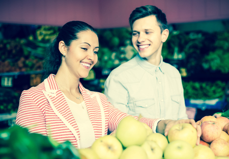 spouses: Positive young spouses choosing fruits and vegetables in market and smiling
