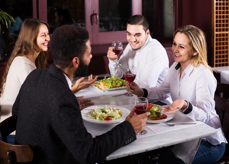 european people: smiling middle class european people enjoying food in cafe and talking Stock Photo