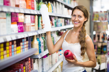 Adult beautiful woman in good spirits selecting shampoo in the store Stock Photo