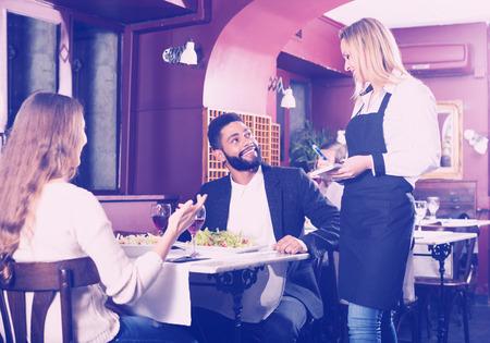 middle class: cónyuges sonrientes positivos que tiene fecha en el restaurante de clase media