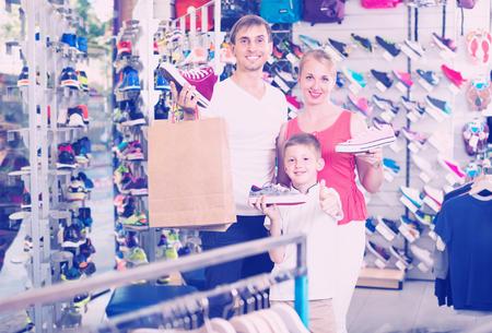 comprando zapatos: smiling parents with schoolboy son buying new sport shoes in sport supermarket Foto de archivo