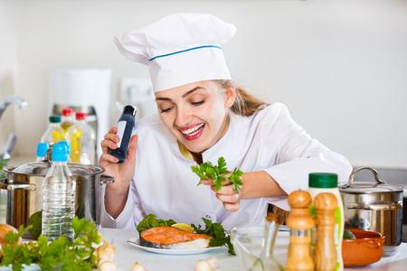 jorobado: positivo plato de chef profesional que adorna con salmón para el cliente