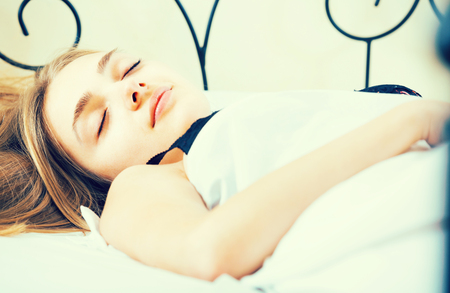 doze: Portrait of charming young woman sleeping in bed Stock Photo