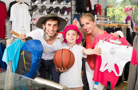 russian man: smiling russian man and woman with boy choosing all for hiking in sport shop