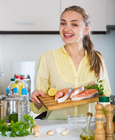 jorobado: Mujer con la preparación de pelo largo plato de trucha en el hogar