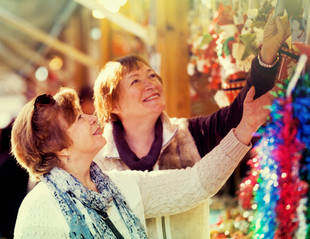 Cheerful mature women walking on the Christmas market and choosing jewelry Stock Photo