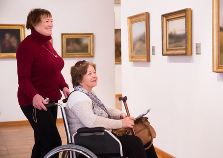 75s: Elderly woman and senior disabled friend in art gallery