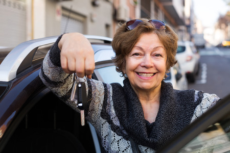 vestidos antiguos: Portrait of happy elderly woman with keys near car
