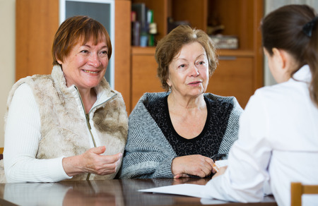 therapeutist: Senior women discussing health problems with therapeutist in clinic