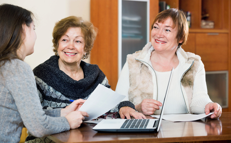 75s: Elderly positive women making will at public notary office and smiling
