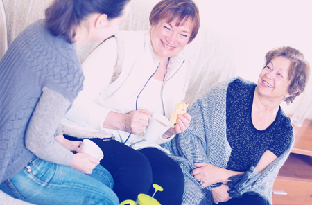 70s: Portrait of adult girl and two pensioners drinking tea together Stock Photo