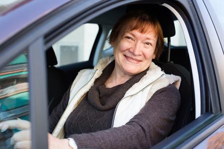 75s: Portrait of happy american female senior driver smiling in car
