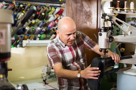atelier: Professional shoemaker stitching footwear on machine in shoe atelier