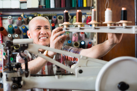 broaching: Mature  positive smiling workman sewing leather boots on stitch lathe in workshop