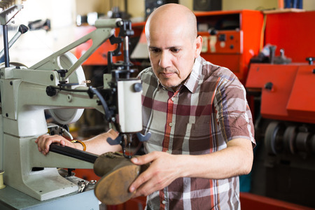 clicker: Professional repairman stitching footwear on machine in shoe atelier Stock Photo
