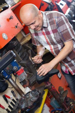 footwear: Professional efficient  friendly shoemaker heeling footwear on machine in workshop