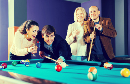 Attractive group of friends of different ages playing billiards and smiling in night club Banque d'images