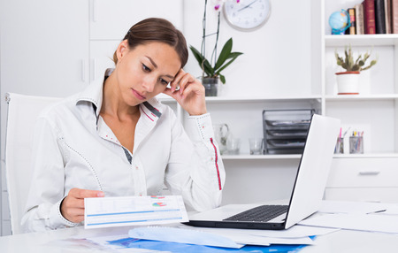 depressed young woman sitting with computer and having work troubles in office