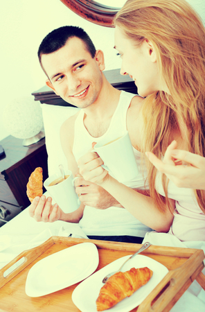 Happy smiling man and positive girlfriend with tasty breakfast in bed