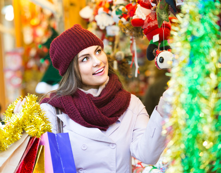 overspending: Portrait of adult female customer near counter with Christmas gifts