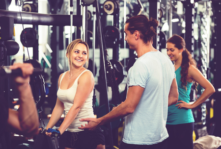 powerlifting: Cheerful young adults doing powerlifting on machines in modern fitness club
